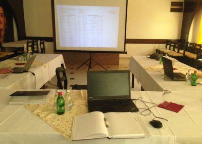 Slika stola na kome se nalazi laptop preko koga se pušta prezentacija tokom jedne konferencije