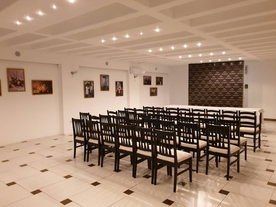 Slika kongresne sale sa poređanim stolicama