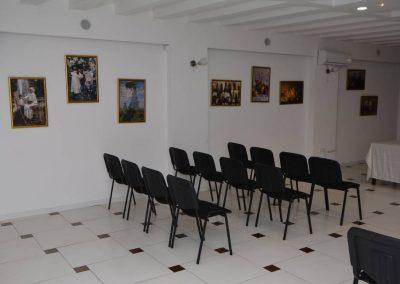 Slika kongresne sale sa poređanim crnim stolicama