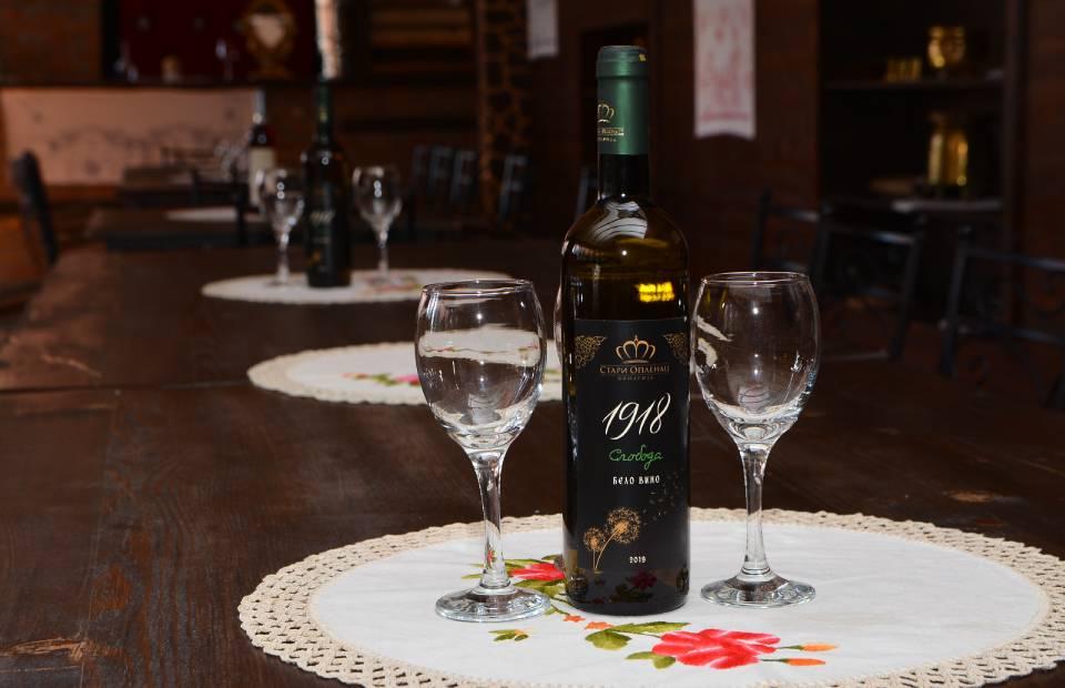 Slika flaše belog vina i dve vinske čaše na stolu