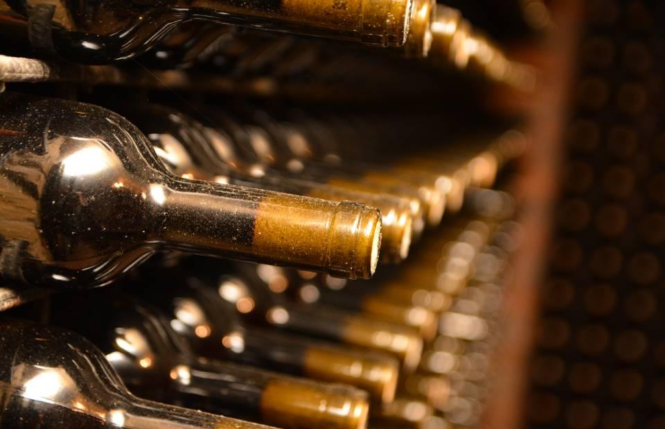 Slika flaša vina na polici sa zlatnim vrhovima