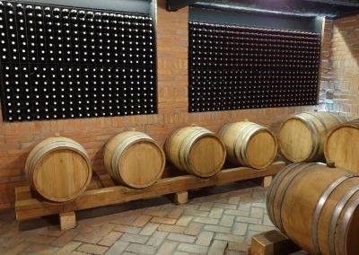Slika buradi gde stoji vino i police sa flašama vina