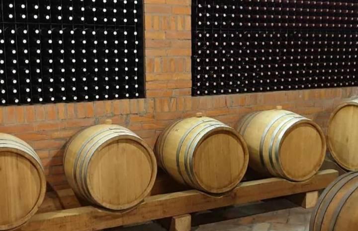 Vinski podrum sa nekoliko buradi u kojima je vino i policama sa vinskim flašama
