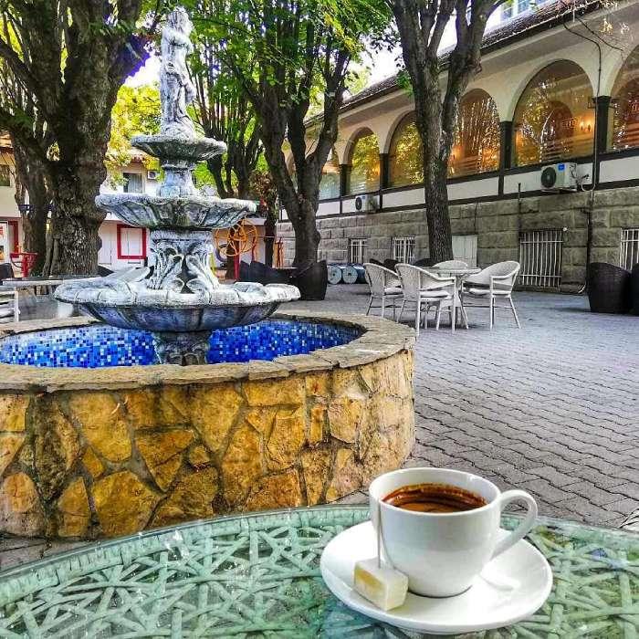 Šoljica kafe na stolu sa ratlukom pored fontane