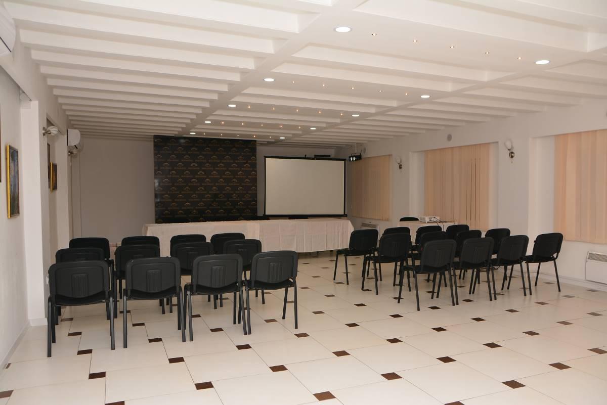 Kongresna sala sa crnim stolicama i velikim belim platonm