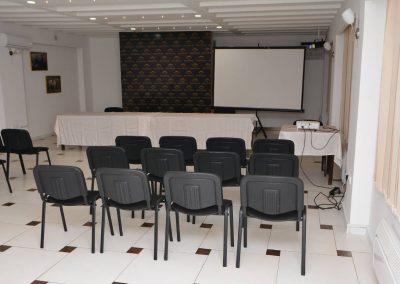 Crne stolice lepo poređane za predavanje u kongresnoj sali