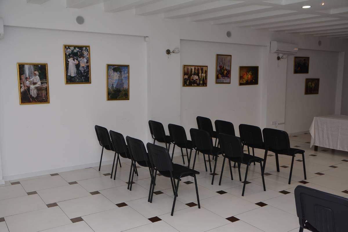 Crne stolice u kongresnoj sali sa slikama na belom zidu