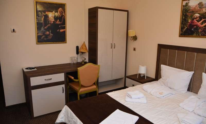 Slika atraktivne retro sobe za dvoje sa ormanom i stalažom u ćošku sobe