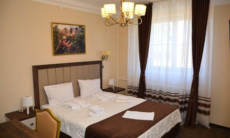 Bračni krevet sa ljubičastim pokrivačem i slikom iznad kreveta