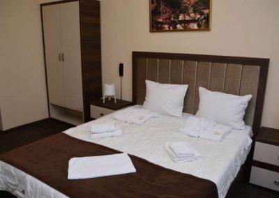 Slika bračnog kreveta sa peškirom na njemu i komodom sa strane na kojoj se nalazi lampa