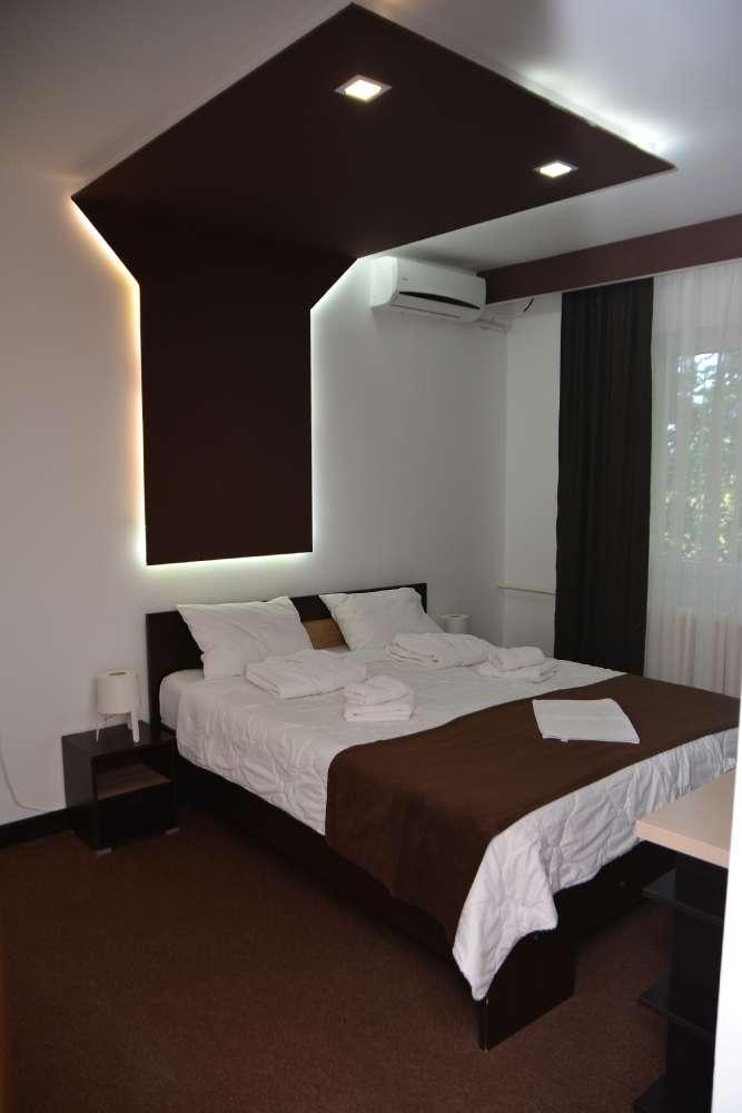 Slika bračnog kreveta sa belom posteljinom i ljubičastim pokrivačem i renoviranim zidnim svetlima