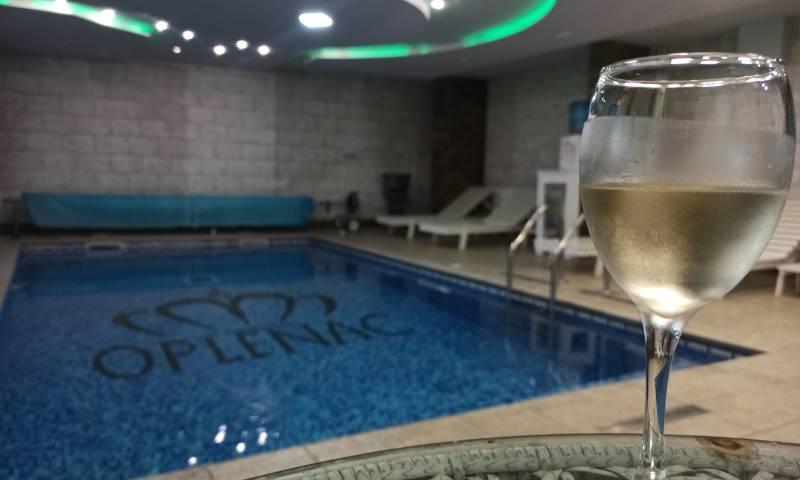 Noćno kupanje u bazenu sa čašom vina na stolu pored