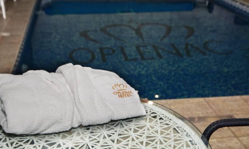 Beli bade mantil na stolu pored bazena sa logom hotela