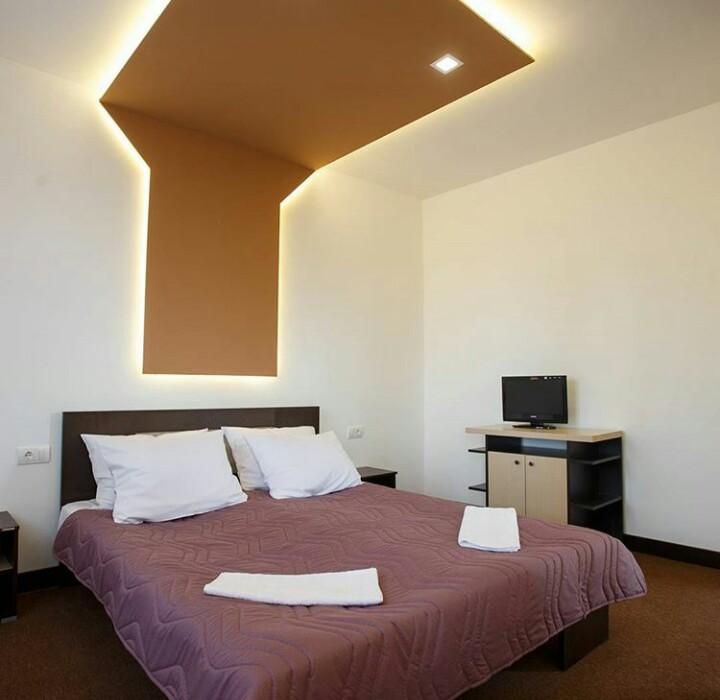 Slika bračnog kreveta sa ljubičastom posteljinom i dva peškira na njemu
