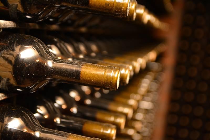 Vinske flaše na stalcima u podrumu vina