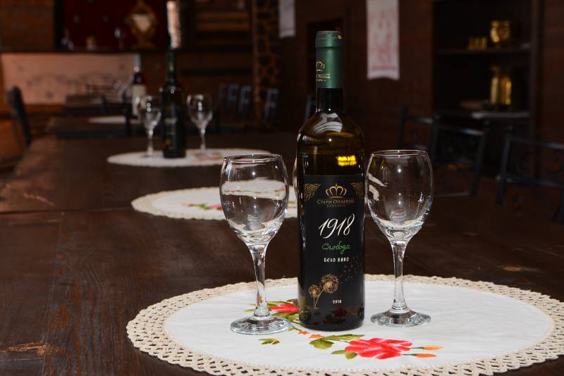 Flaša belog vina između dve vinske čaše